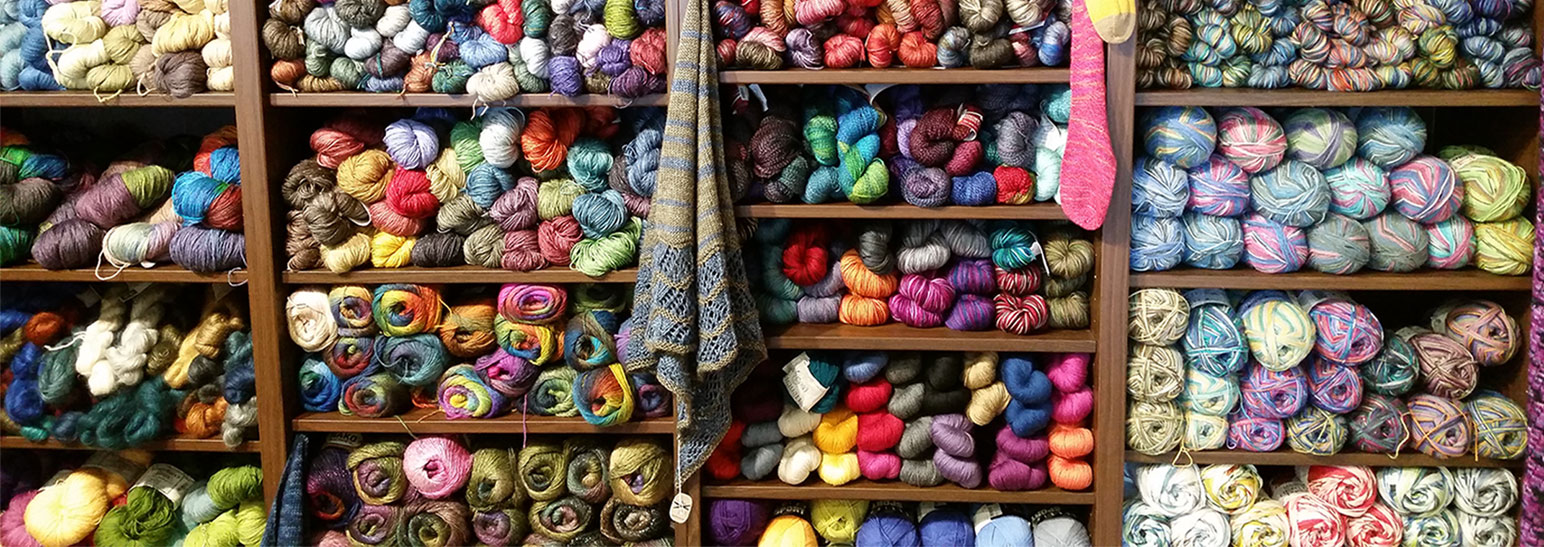 A wall full of colorful yarn at a store.